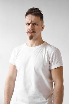Homem rabugento hipster com bigode elegante e barba, franzindo a testa e olhando para a câmera com expressão facial de raiva, estando insatisfeito com a qualidade do produto ou serviço. reação humana negativa