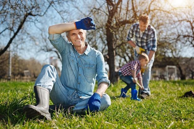 Homem radiante sênior usando luvas de jardim e botas de borracha, sentado na grama enquanto relaxa com seu filho e neto cavando ao fundo