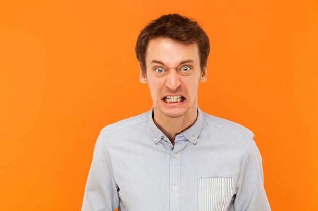 Homem raivoso com olhos grandes olhando para a câmera
