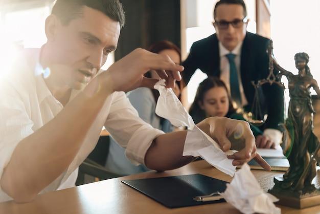Homem rasga contrato de casamento enquanto está sentado ao lado de mulher