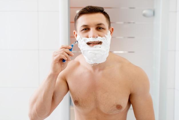 Homem raspa a barba com navalha no banheiro, higiene matinal de rotina.