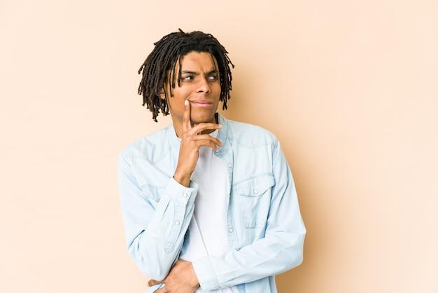 Homem rasta jovem afro-americano contemplando, planejando uma estratégia, pensando