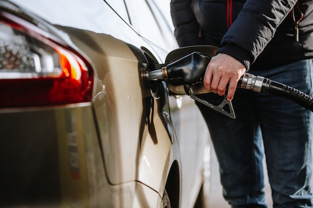 Homem reabastecendo seu carro no posto de gasolina ou posto de gasolina com nafta ou óleo combustível, processo de abastecimento