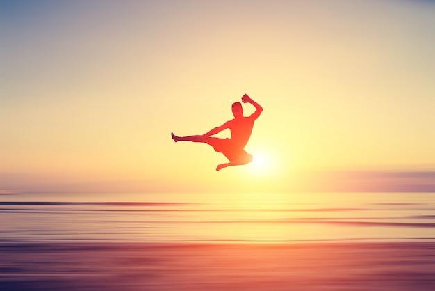 Homem realizando chute alto na praia