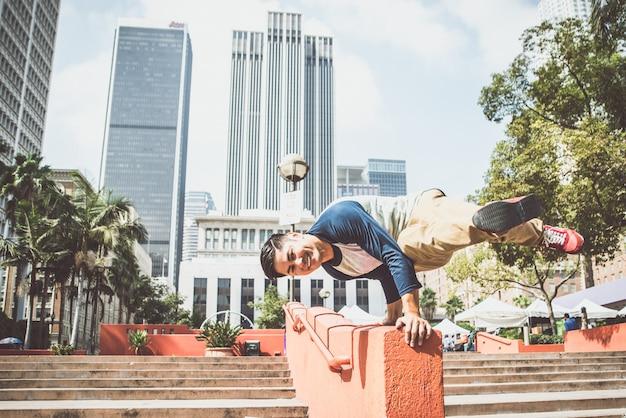 Homem realizando truques de parkour no centro urbano