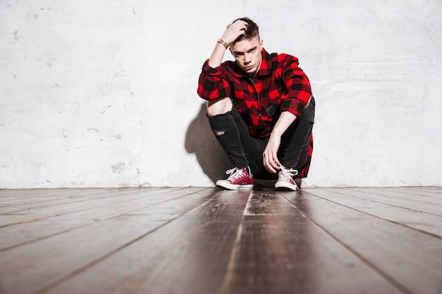 Homem rebelde na camisa xadrez posando sentado perto da parede