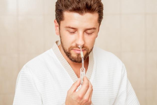 Homem recebe inalação nasal de óleo essencial no spa.