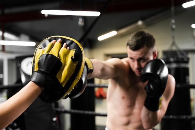 Homem recebendo ajuda no treinamento duro para uma competição de boxe