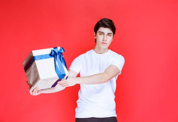 Homem recebendo e segurando uma caixa de presente branca embrulhada com fita azul com as duas mãos