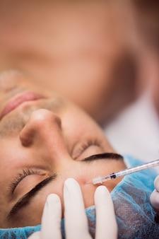 Homem recebendo injeção de botox na testa