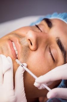 Homem recebendo injeção de botox nos lábios