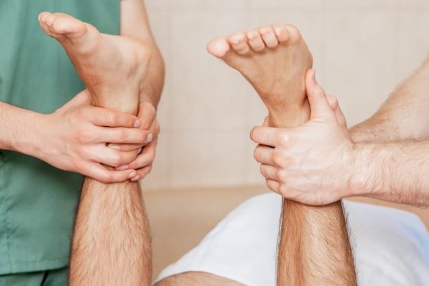 Homem recebendo massagem nas pernas.