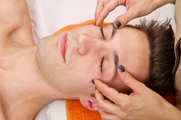 Homem recebendo massagem no centro de beleza