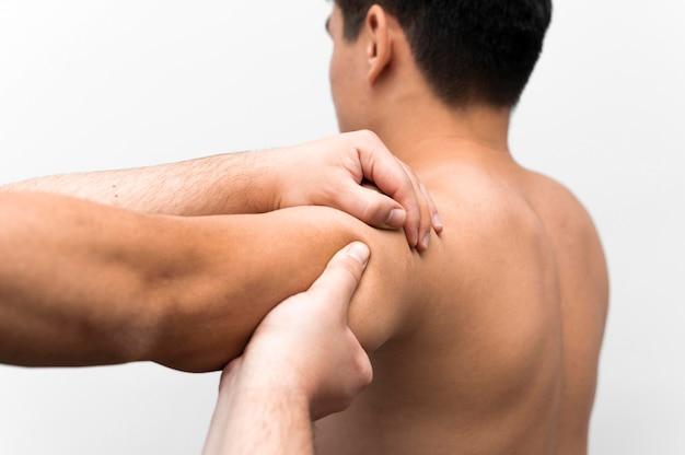 Homem recebendo massagem no ombro do fisioterapeuta