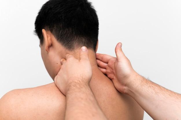 Homem recebendo massagem no pescoço com fisioterapeuta