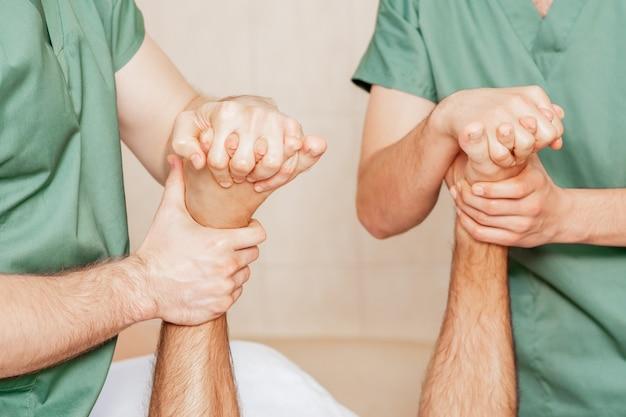 Homem recebendo massagem nos dedos do pé.