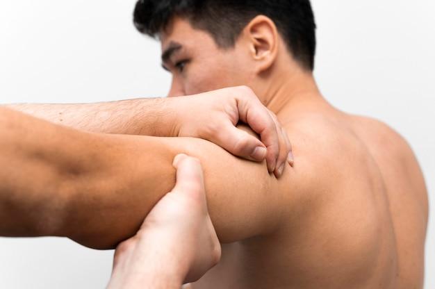 Homem recebendo massagem para dor no ombro com fisioterapeuta