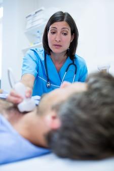 Homem recebendo ultra-som de um tiróide de médico