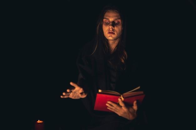 Homem recitando um livro de feitiços vermelho no escuro