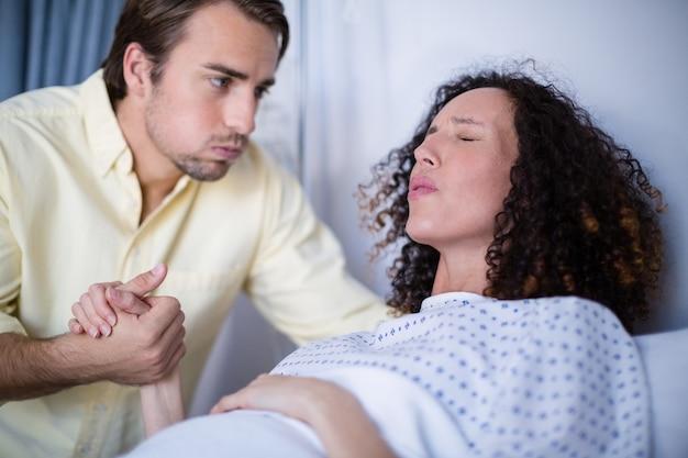Homem reconfortante mulher grávida durante o parto na enfermaria