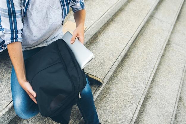 Homem recortado, colocando o laptop na caixa do laptop depois de trabalhar ao ar livre
