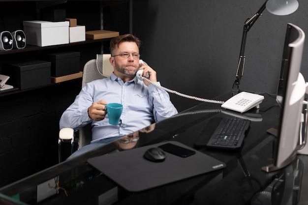 Homem recostou-se na cadeira, tomando café e falando em telefone fixo
