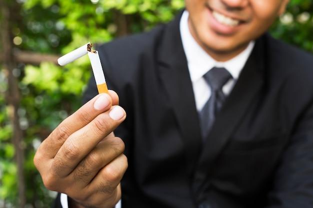 Homem recusando o conceito de cigarros para parar de fumar e estilo de vida saudável escuro.