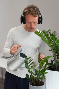 Homem regando plantas tiro médio