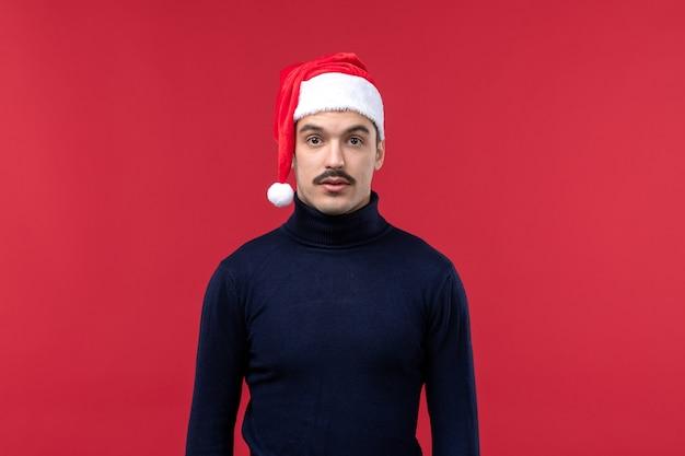 Homem regular de vista frontal com camisa escura e tampa vermelha sobre fundo vermelho