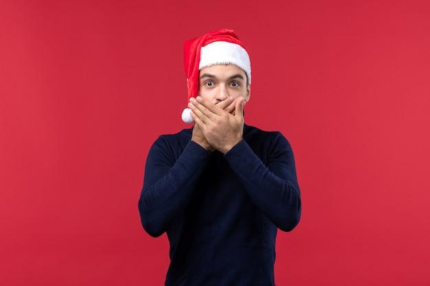 Homem regular de vista frontal com expressão chocada em fundo vermelho