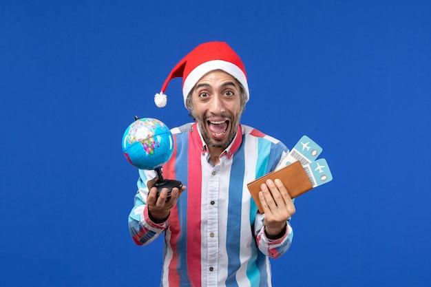 Homem regular de vista frontal com globo e ingressos na parede azul emoções feriado ano novo