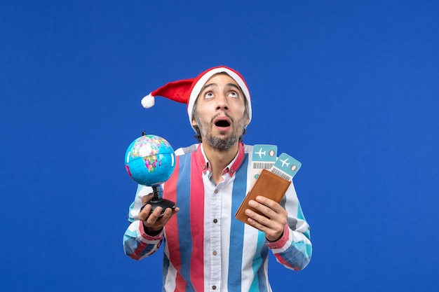 Homem regular de vista frontal com ingressos e globo no piso azul, cor do feriado de ano novo