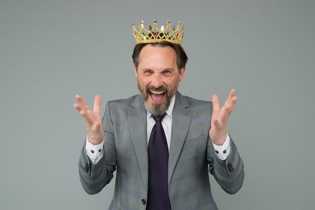 Homem rei emocional usando coroa de ouro, sentir o conceito de poder.