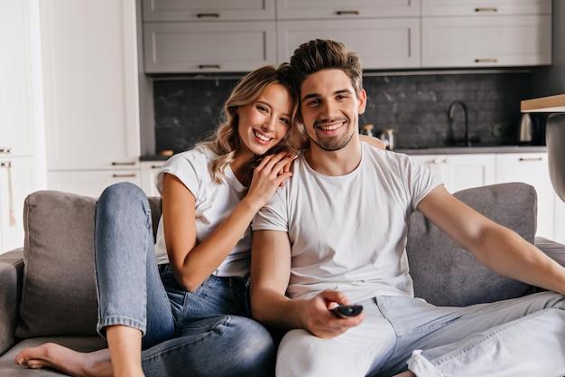 Homem relaxado assistindo tv. menina loira graciosa sentada no sofá com o marido.