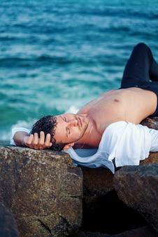 Homem relaxado deitado em uma rocha na praia
