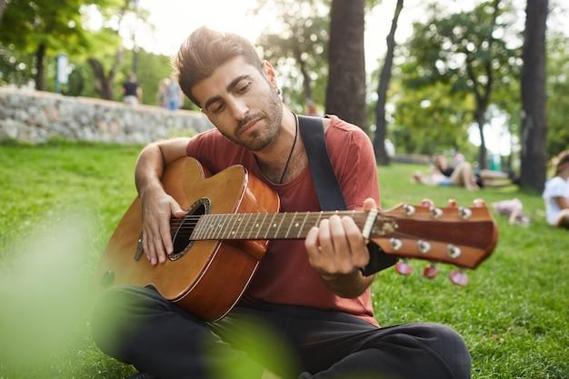 Homem relaxado e sonhador tocando violão, sentado na grama no parque com um instrumento