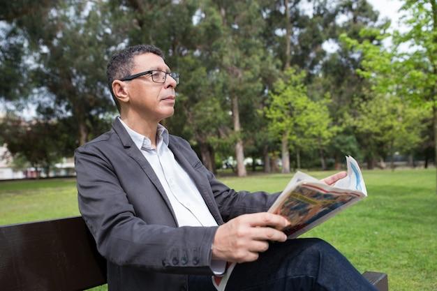 Homem relaxado, lendo jornal e sentado no banco no parque