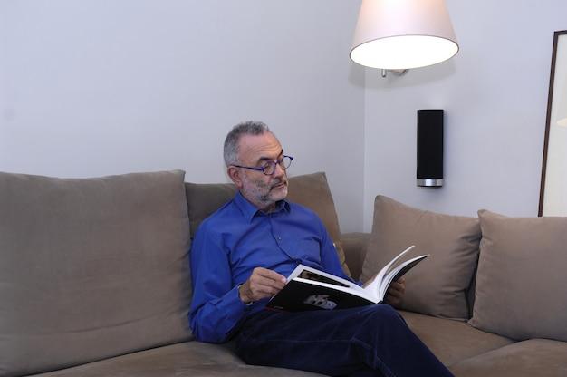 Homem relaxando e lendo em um sofá