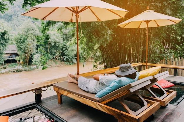 Homem relaxando em uma cadeira de praia perto do lago