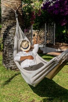 Homem relaxando em uma rede no jardim.