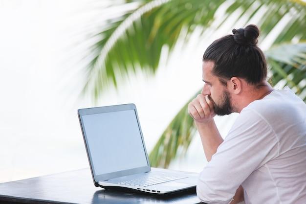 Homem relaxando na praia com o trabalho dos sonhos de freelancer laptop no local de trabalho