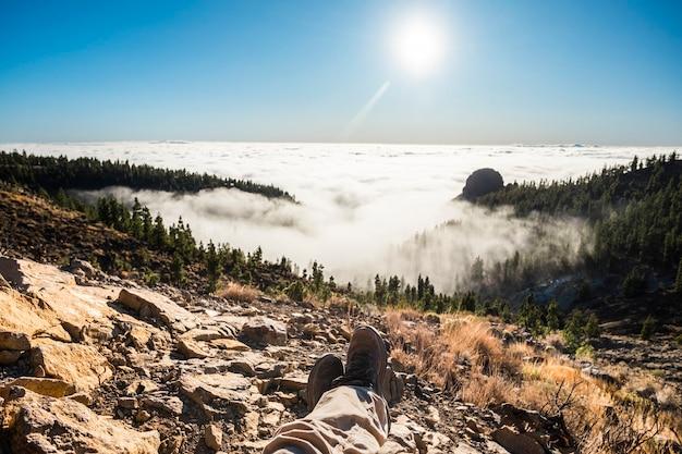Homem relaxando no topo de uma montanha com excelente vista da paisagem