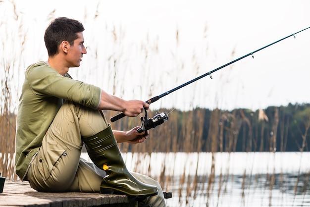 Homem relaxando, pescando ou pescando no lago, sentado de pernas cruzadas no cais