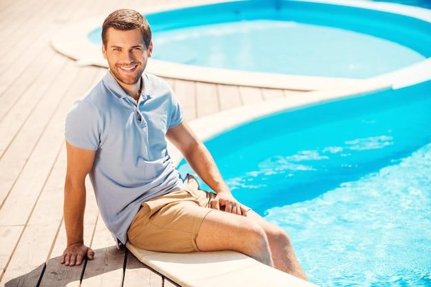 Homem relaxante à beira da piscina. jovem bonito em camisa pólo sentado à beira da piscina e sorrindo