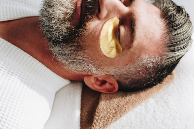 Homem relaxante com um tratamento de máscara de olho dourado