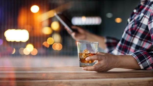 Homem relaxante com uma bebida de uísque de bourbon