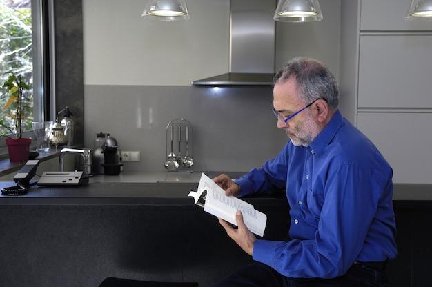Homem relaxante e lendo em uma cozinha
