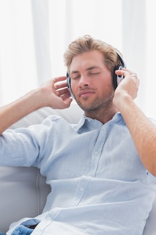 Homem, relaxante, enquanto, escutar música, ligado, um, sofá, em, a, sala de estar