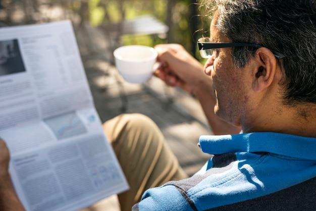 Homem, relaxante, enquanto, leitura, um, jornal, e, café bebendo