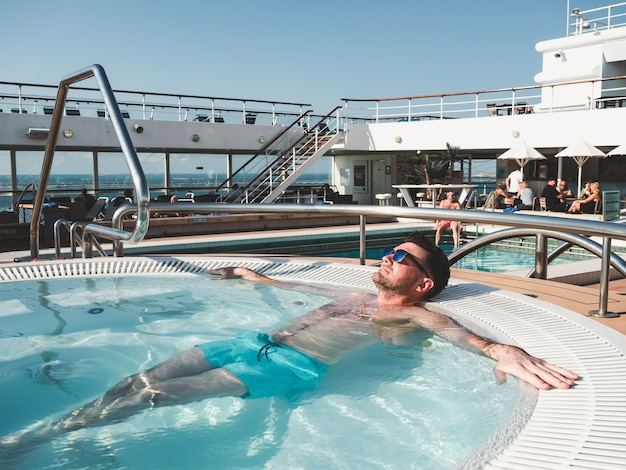 Homem relaxante na piscina no convés